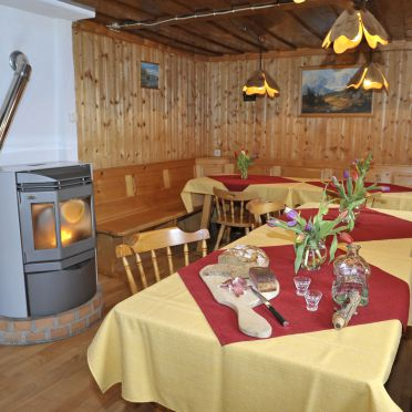 Hoamatlhütte, livingroom with diningtables and oven