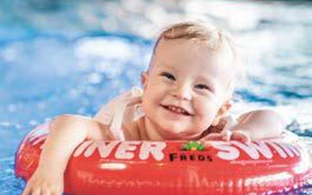 Kleinkind hat Spaß im Schwimmbad des Familienhotels